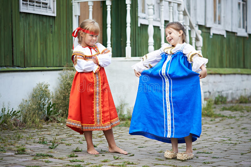 Two girls in national costumes in Russian village. On summer day royalty free stock photo