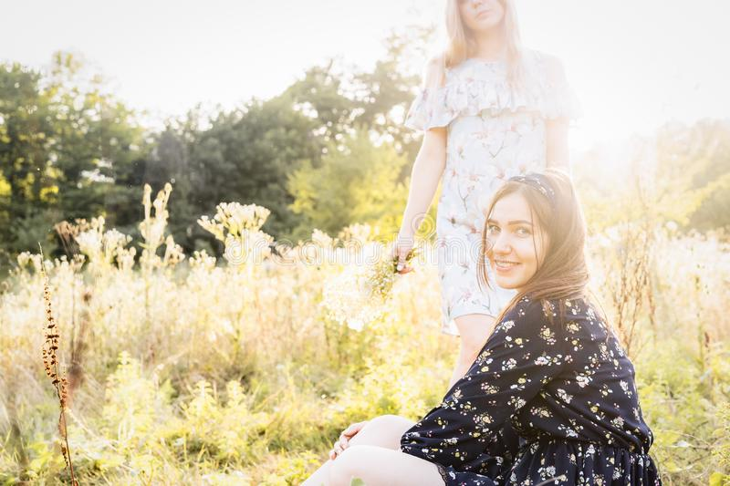 Two girls on nature in high grass stock photography
