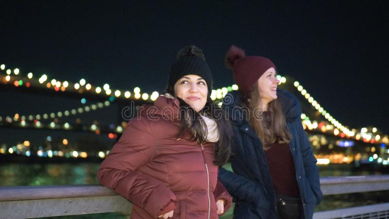 Two girls in New York enjoy the most beautiful place in the city at Brooklyn Bridge stock photo
