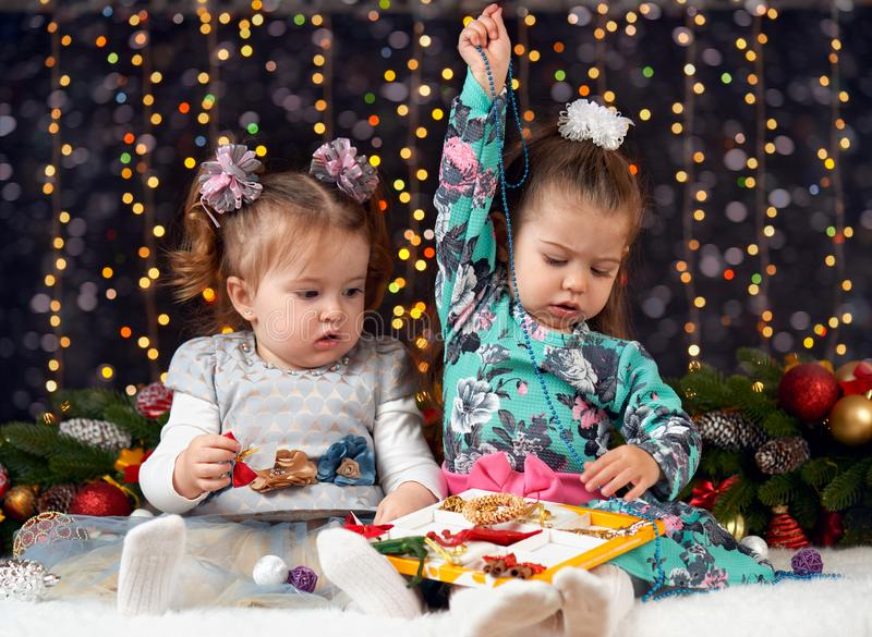 Two girls open gift boxes in christmas decoration, dark background with illumination and boke lights, winter holiday concept royalty free stock image
