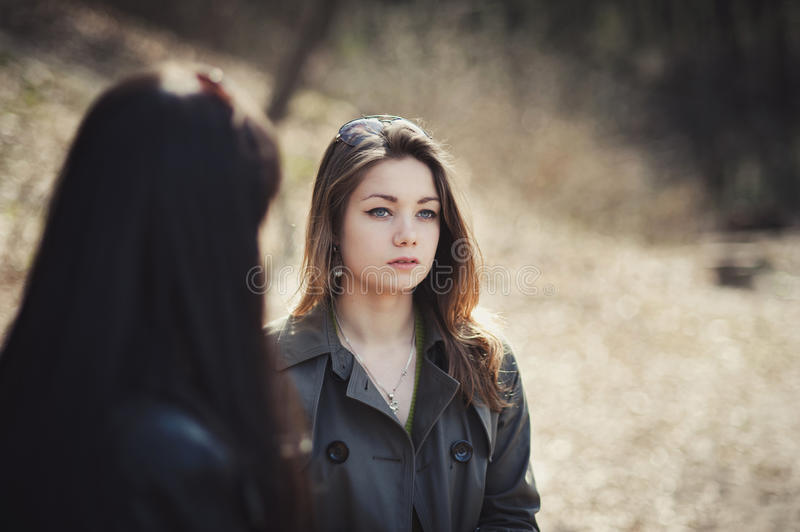 Two girls opposite each other in an autumn park royalty free stock photography