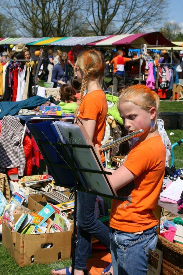 Two girls in orange t-shirts at the Vrijmarkt during Kingsday (Koningsdag),Amsterdam stock photo