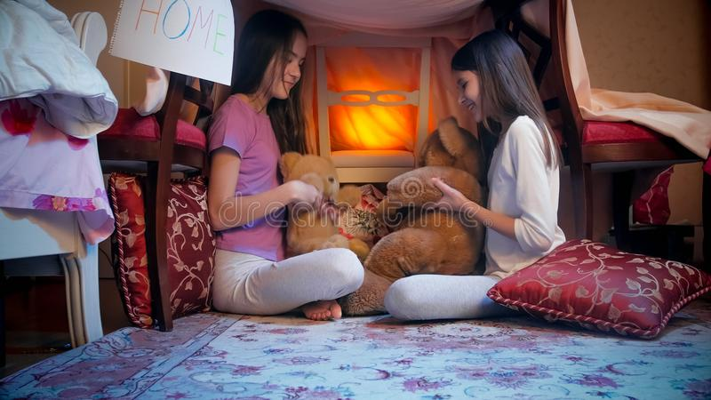 Two cute girls in pajamas playing in selfmade tent with teddy bears. Two girls in pajamas playing in selfmade tent with teddy bears stock image