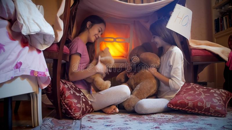 Two cute girls in pajamas playing with teddy bears in bedroom at night. Two girls in pajamas playing with teddy bears in bedroom at night stock photos