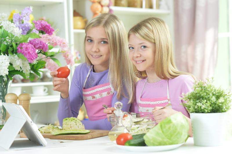 Two girls in pink aprons preparing fresh salad. On kitchen table with tablet royalty free stock images