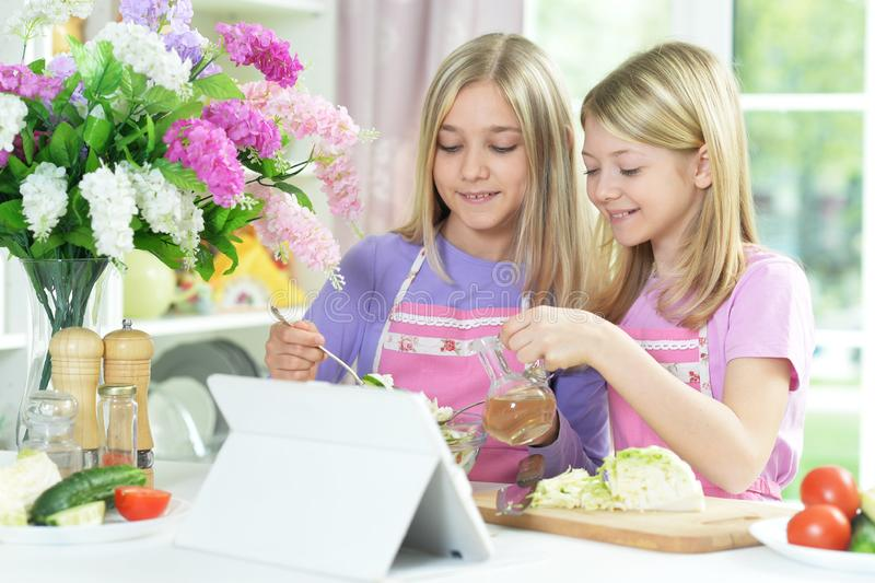 Two girls in pink aprons preparing fresh salad. On kitchen table with tablet stock photos