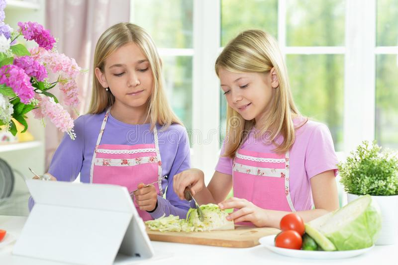 Two girls in pink aprons preparing salad. On kitchen table with tablet stock photography
