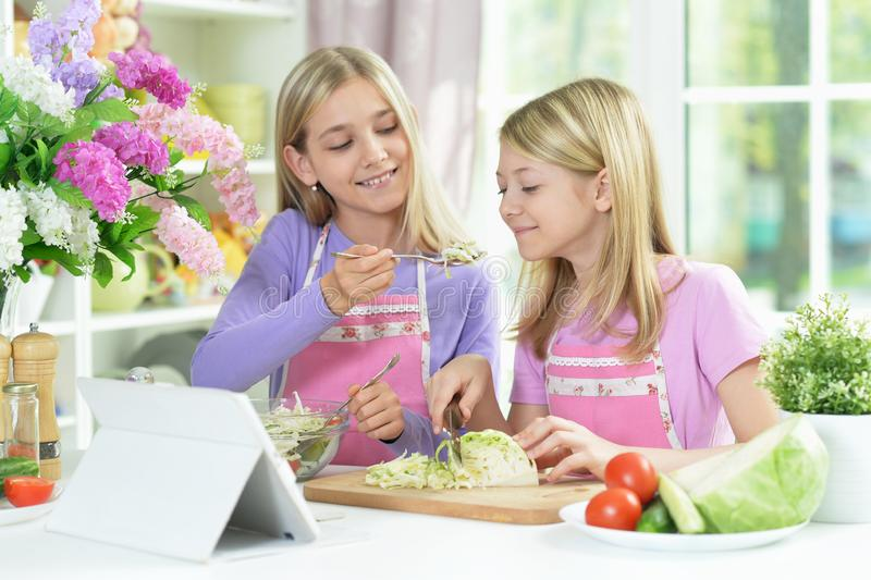 Two girls in pink aprons preparing salad. On kitchen table with tablet stock images