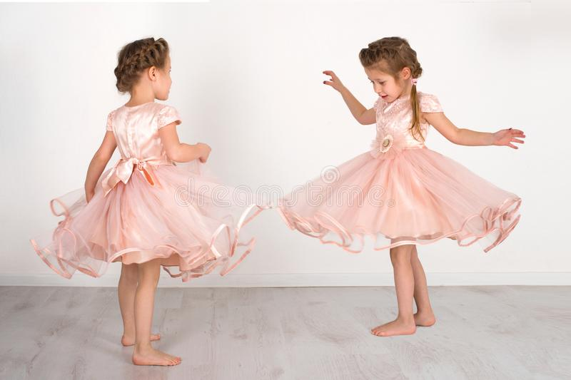 Two girls in a pink ball dress to be turned in dance. Two little girl in a pink ball dress to be turned in dance royalty free stock photos
