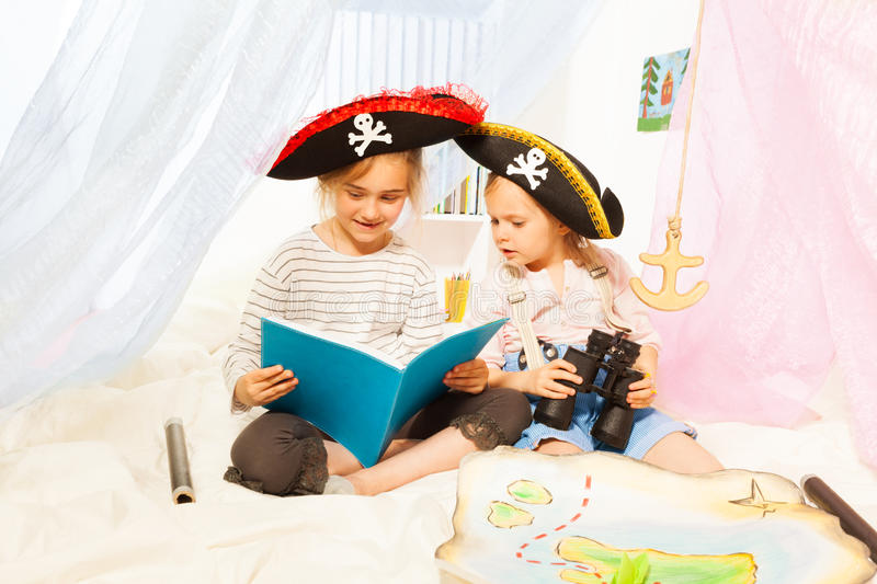 Two girls in pirate's costumes reading fairy-tale royalty free stock photography