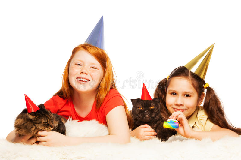 Two girls play party game with their cats royalty free stock photo