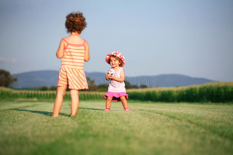 Two girls playing with ball stock photography