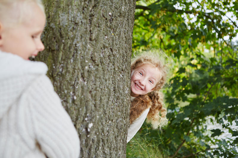 Two girls playing hide and seek stock photo
