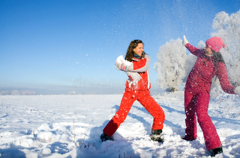 Two girls playing with snow stock photos