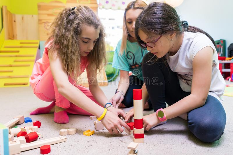 Two girls playing together with wooden toy blocks on the floor d stock images