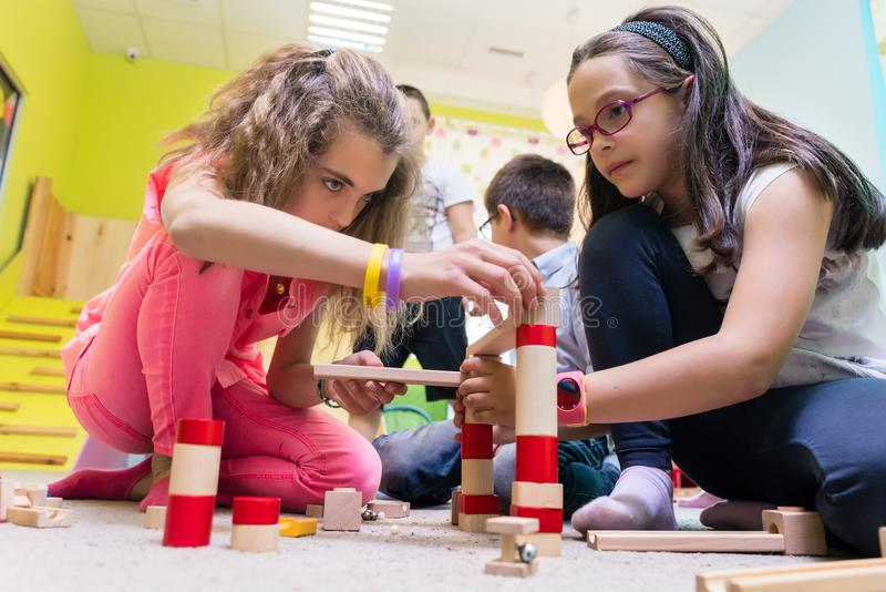 Two girls playing together with wooden toy blocks on the floor at kindergarten stock image