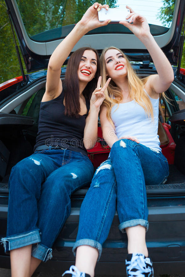 Two girls posing in car. Resting in the country. taking a trip somewhere by car. Girls taking selfie royalty free stock photos