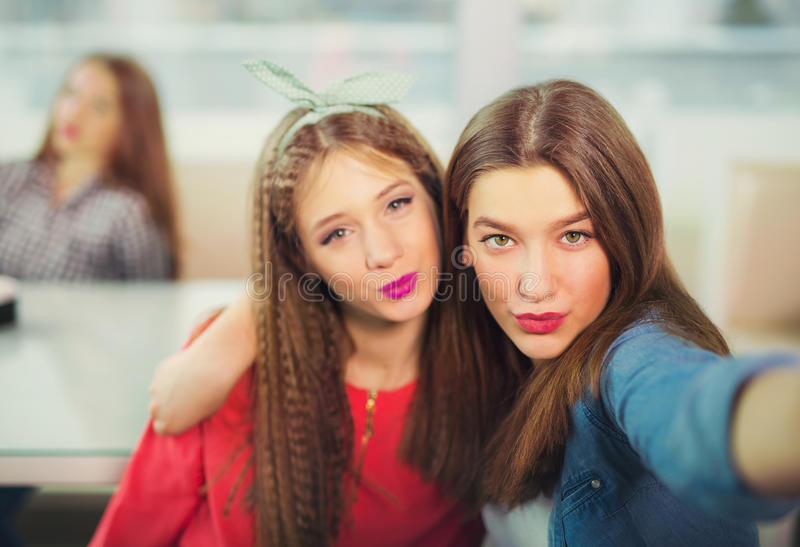 Two girls pouting while taking a selfie photo on mobile phone stock photography