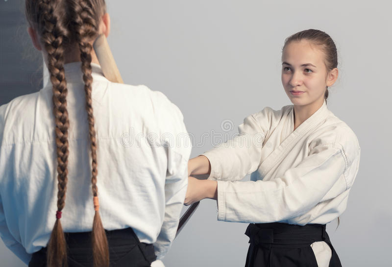 Two girls practice sword on Aikido training. On white background. Selective focus stock photo