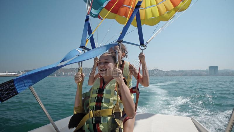 Two girls prepare for take off from boat at parasailing. At Beach stock photography