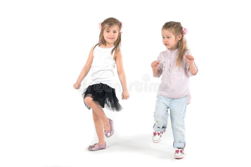 Two girls play outdoor games or dance. Two girls preschooler play outdoor games or dance. The picture on white stock image
