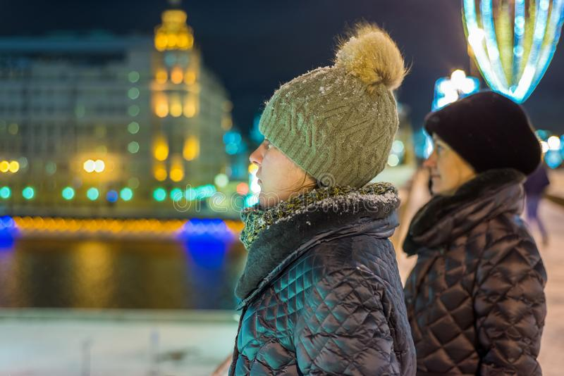 Two girls in profile in winter clothes at night on the street. In the background is a festive Christmas illumination stock photography
