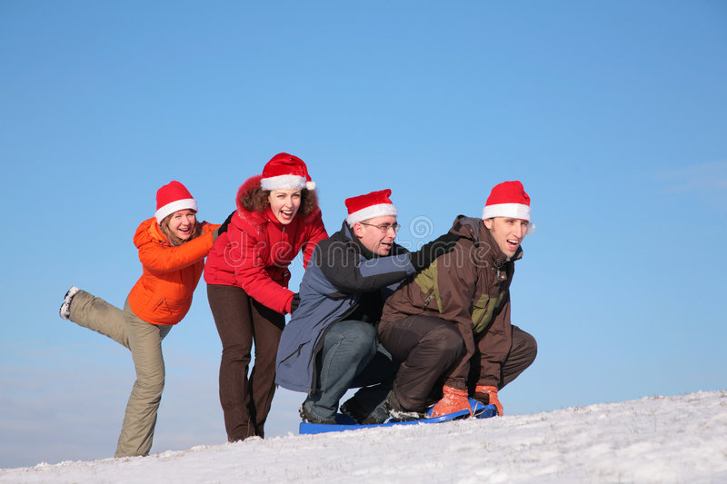 Two girls push two men on sled. In winter stock image