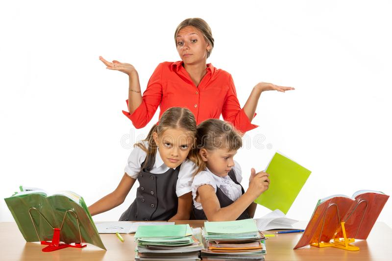 Two girls are pushing while sitting at a desk, the teacher does not know what to do with it stock photo