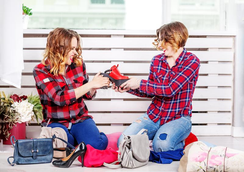 Two girls quarrel for shoes. The concept of fashion, style, frie. Ndship stock photos