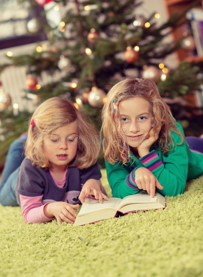 Two girls reading a book in front of christmas tree stock photography