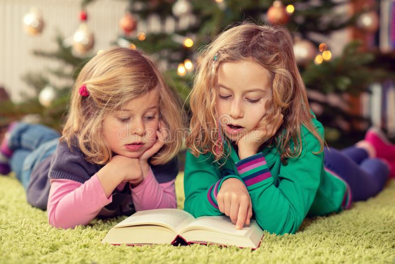 Two girls reading a book in front of christmas tree stock photo