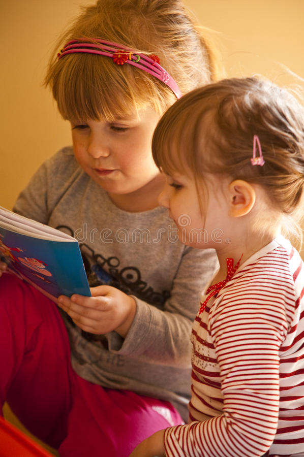 Two girls reading book stock photo