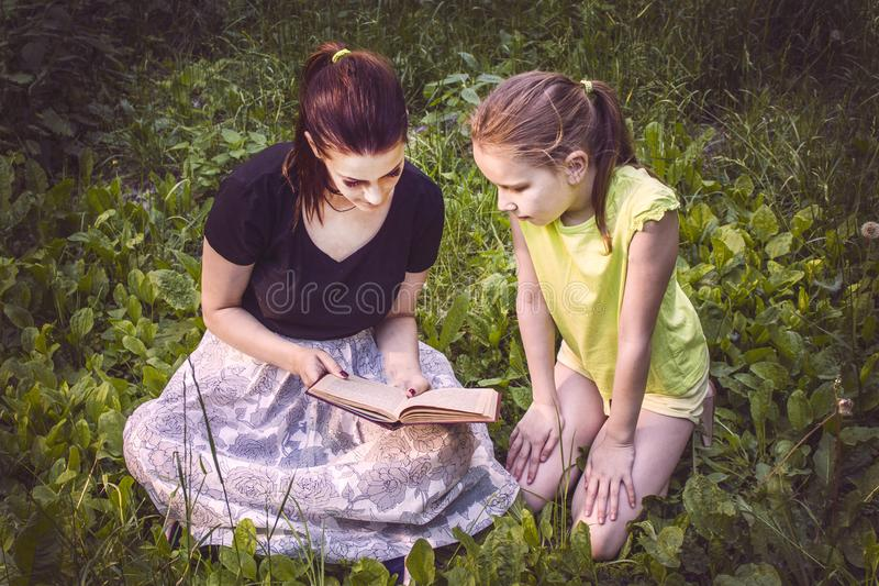Two girls are reading a book sitting on the grass stock image