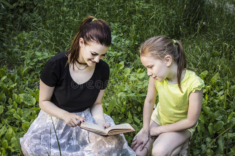 Two girls are reading a book sitting on the grass stock photo