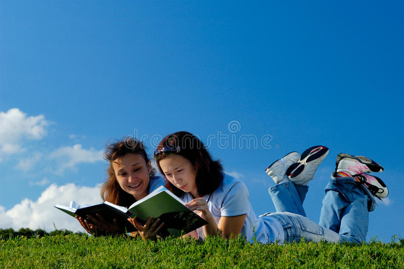 Two girls reading books outside. Two happy girls reading books in the nature studying outside in a park lying on green grass royalty free stock image