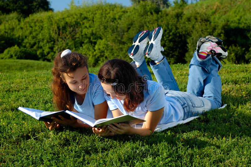 Two girls reading books outside in a park. Two girls lying on the grass studying outdoors in the nature reading books stock photography