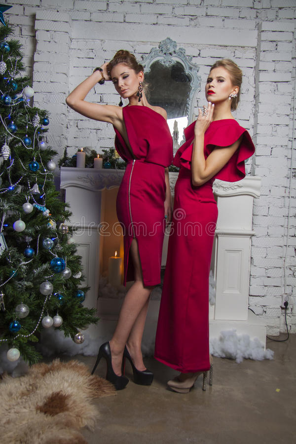 Two Girls in red party dress near new year tree. Girsl in red party dress standing straight and posing in studio stock images