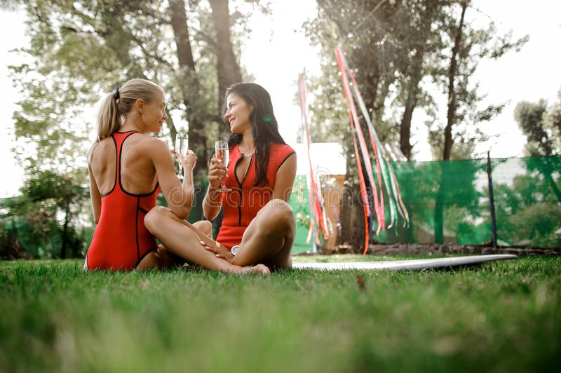 Two girls in red swimsuits sitting and drink champagne. Two young girls, blonde and brunette, in red swimsuits sitting on the green grass and drink champagne royalty free stock photography