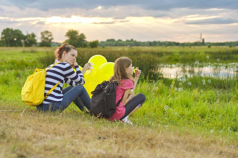 Two girls resting in nature, children with soap bubbles royalty free stock photo