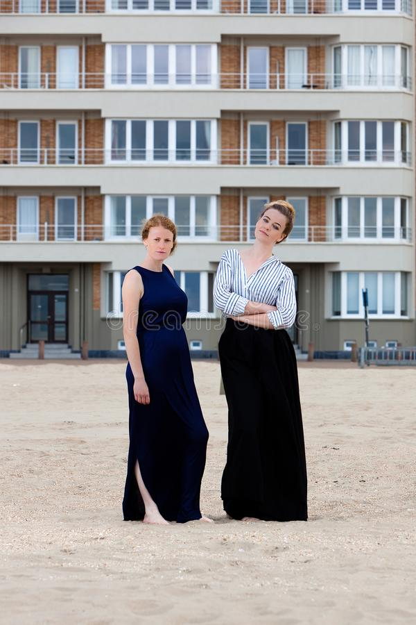 Two girls beach sand apartment building, De Panne, Belgium. Two girls in retro dresses at the beach in front of a art nouveau apartment building in De Panne royalty free stock images