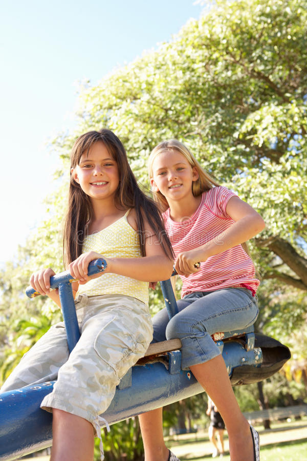 Download Two Girls Riding On See Saw In Playground Stock Photo - Image of nine, friends: 14686338