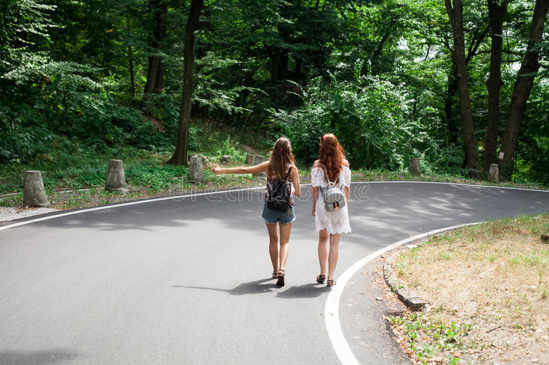 Two girls on a road trip hitchhiking royalty free stock images