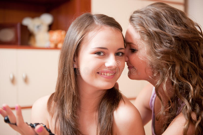 Two girls rumoring. Young girl whispering a secret to her friend stock images
