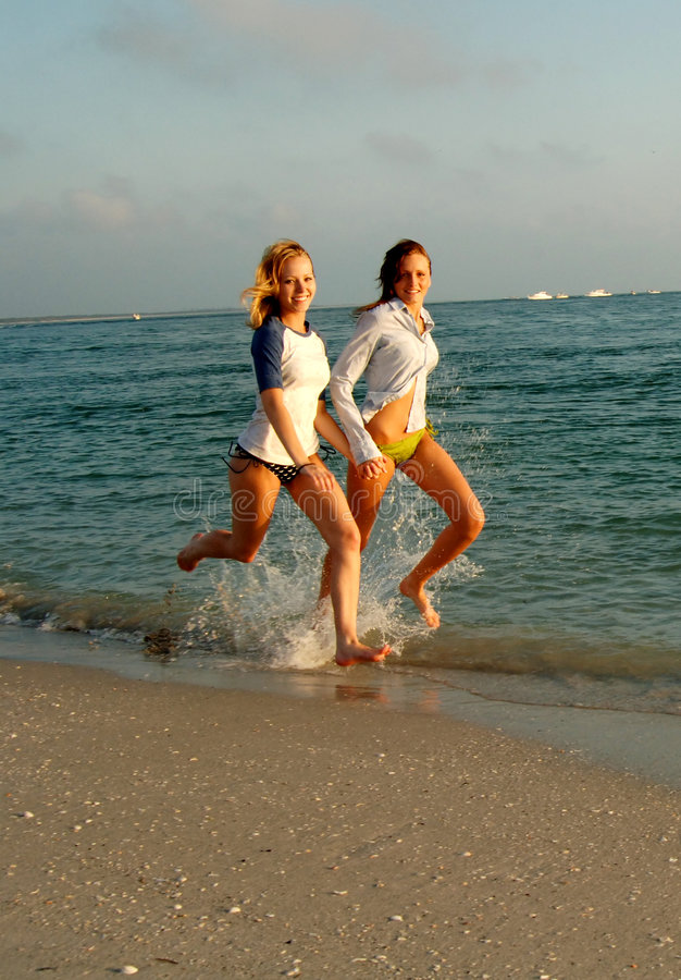 Two Girls Running on the Beach stock photography