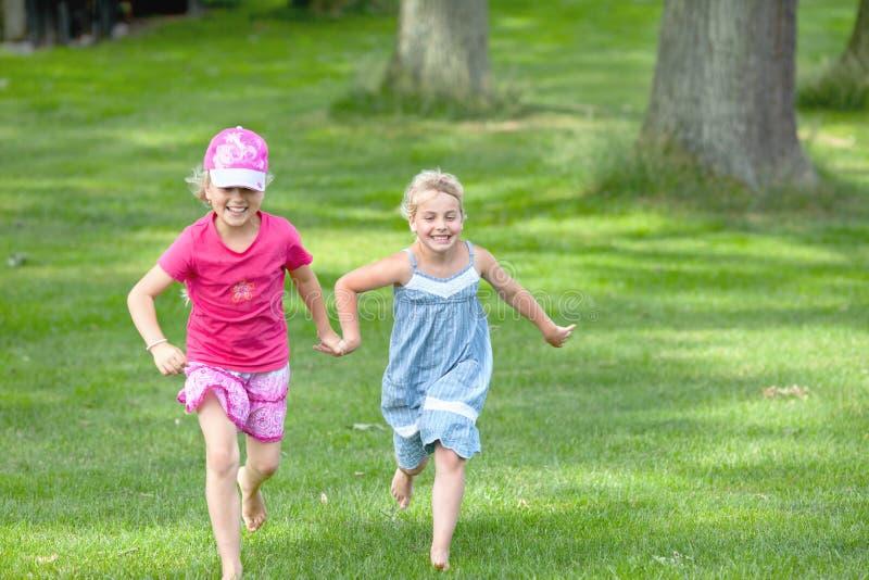 Two girls running happy outdoor stock photos