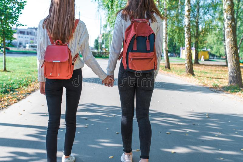 Two girls of schoolgirl of 12-15 years old, in autumn summer day city, returning home on road, view from back, behind royalty free stock photo