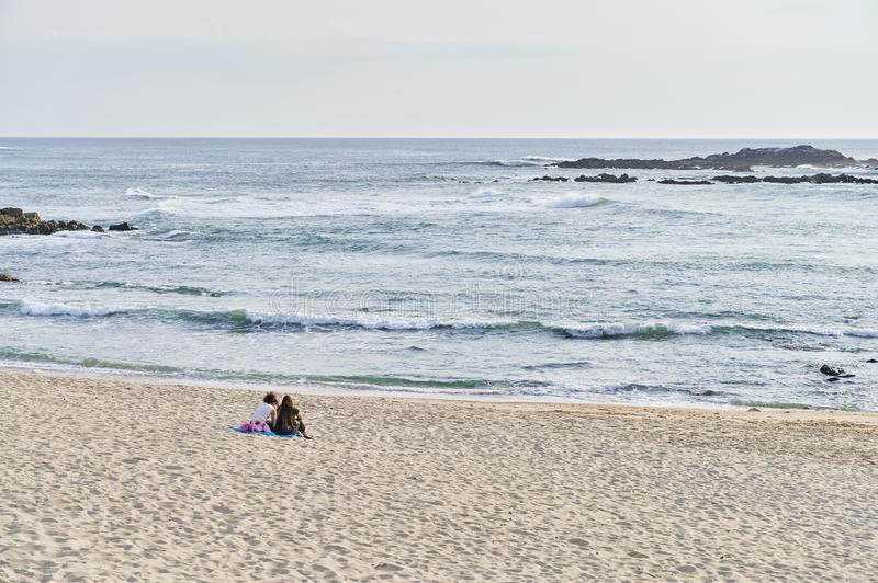 Teenagers seated talking alone on the beach royalty free stock image