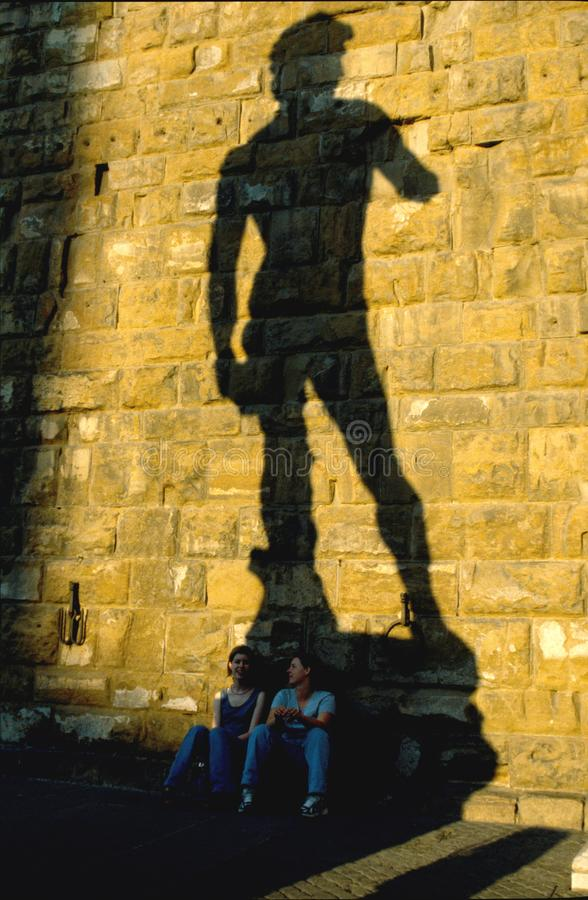 Two girls seated in the shadow of Michelangelo`s David, Florence,Italy.under the stock photography