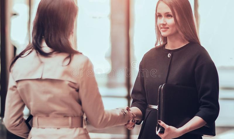 Two girls shaking hands in modern office, smiling and looking at stock images