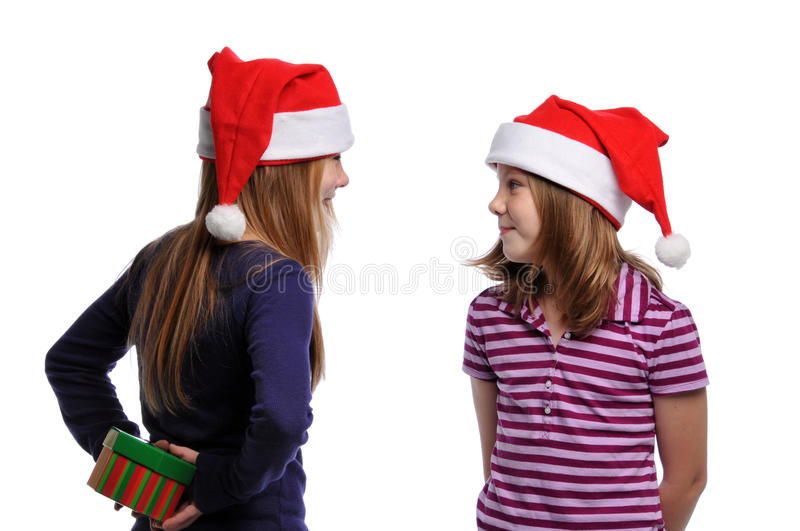 Two girls sharing a Christmas present royalty free stock photo